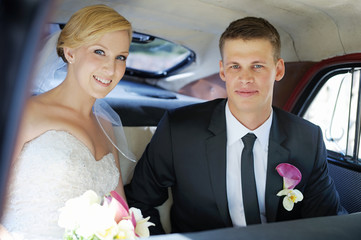 Bride and groom sitting in a car