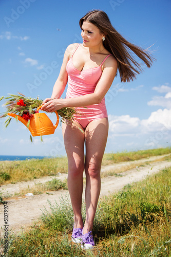 Sexy girl in the field with watering can