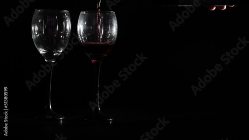 Red wine is poured into two glasses on black background.