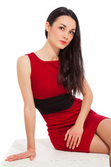 beautiful sexy brunette in red  dress sitting