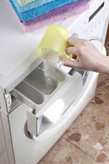 Woman pouring washing powder into the washing machine