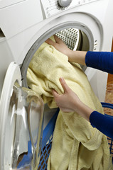 woman hands loading washing machine