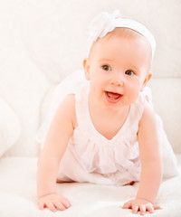 little cute girl in a white dress and with flower smiling
