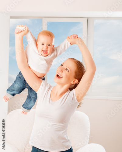 Mother and baby are playing active games, do gymnastics and laug