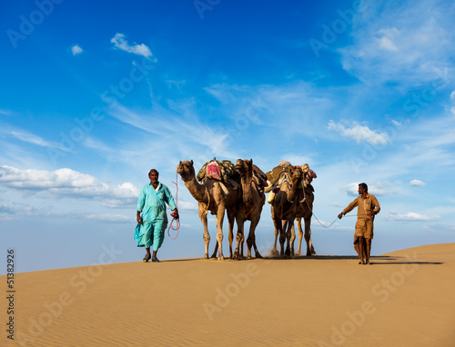 Two cameleers (camel drivers) with camels in dunes of Thar deser