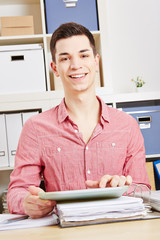 Junger lachender Mann mit Tablet Computer