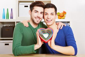 Schwules Paar hält Herz in Regenbogen-Farben