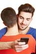 Schwuler Mann umarmt Freund und schaut auf Handy