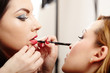 Woman having makeup applied by makeup artist