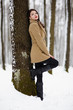 Beautiful brunette leaning on a tree trunk in the winter