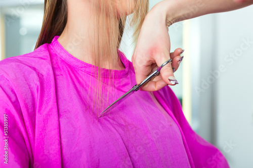 Woman receiving haircut from hairdresser or stylist