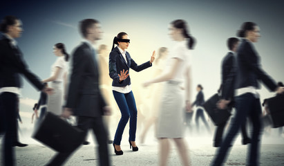 Businesswoman in blindfold among group of people
