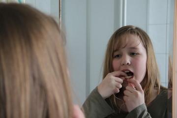 Mädchen wendet Zahnseide an
