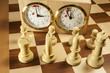 Weiße Schachfiguren vor Schachuhr