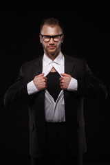business man in glasses tearing off his shirt