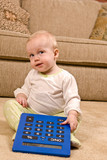 Young baby in pajamas with an over-sized calculator