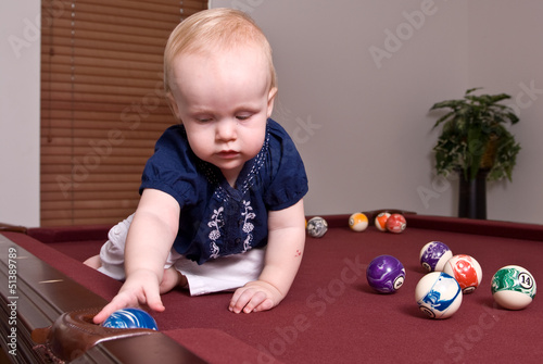 Young child sitting alone on a billiard table