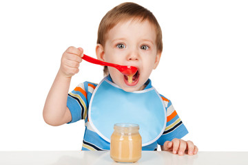 Boy eats with a spoon puree