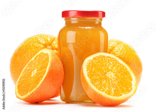 Glass and jug of orange juice, jar of jam and fruits
