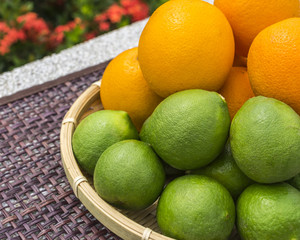 Close up lime and orange fruits in basket