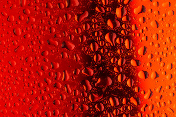 close up water drops on red glass surface