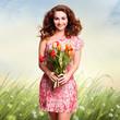 attraktive junge Frau mit Blumenstrauß vor Sommerwiese