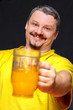 dark smiling man holding a glass of beer