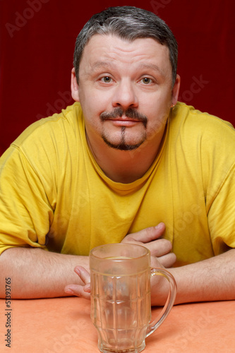 dark man looks at an empty beer mug