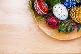 Top view of easter eggs in wooden bowl on wooden backgroud