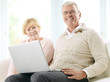 Close up of a senior happy couple in front of a laptop