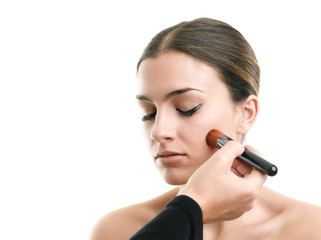 Makeup artist applying makeup against white background