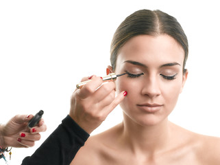 Makeup artist applying eyeliner on eyelid