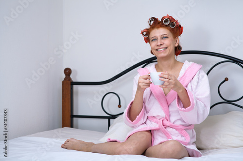 girl in curlers on the bed