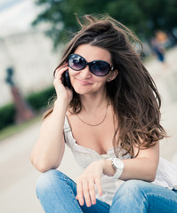 Outdoor portrait of young woman with phone