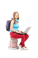 A smiling student with backpack working on a laptop and sitting