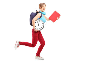 Full length portrait of a female student with clock late for cla