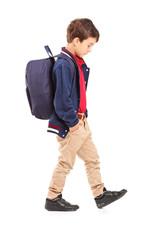 Full length portrait of a sad school boy walking