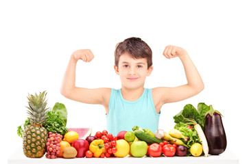 Healthy child showing his muscles and sitting on a table full of