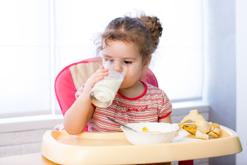 kid girl eating corn flakes with milk
