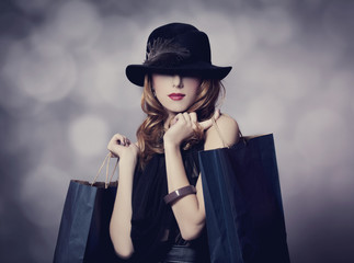Style redhead girl with shopping bags.