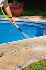 Hosing paving around swimming pool, Spain © Arena Photo UK