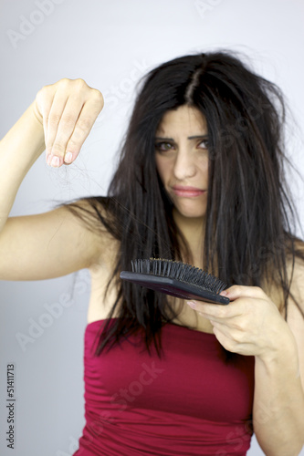 Beautiful woman holding long hair from brushing too hard