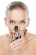 Young beautiful woman holding set of make up brushes, isolated