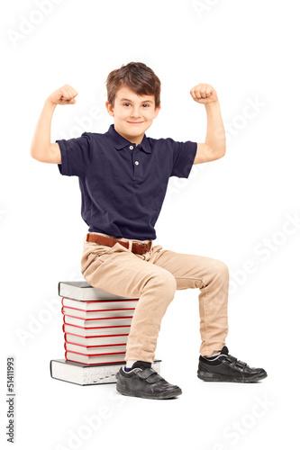 A smiling schoolboy showing his muscles seated on a pile of book