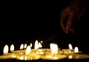 Hand lighting a candle