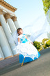 Little bride. A girl in a lush white and blue wedding dress and