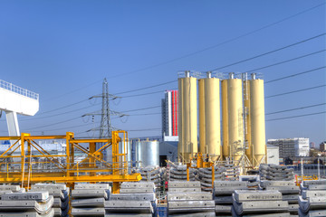 industrial scene with concrete, tanks, plyons and crane