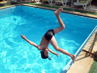 Young boy jumping into pool