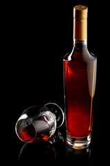 Bottle and glass of cognac over black background