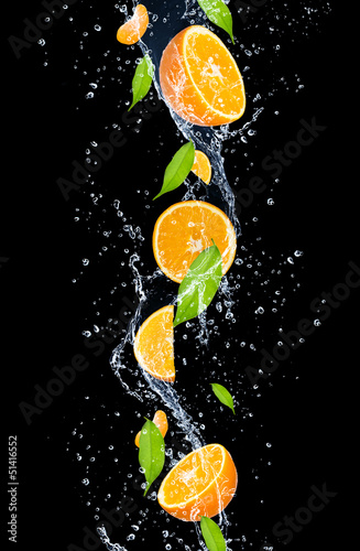pomarancze-w-wodnym-plusnieciu-odosobnionym-na-czarnym-backgro